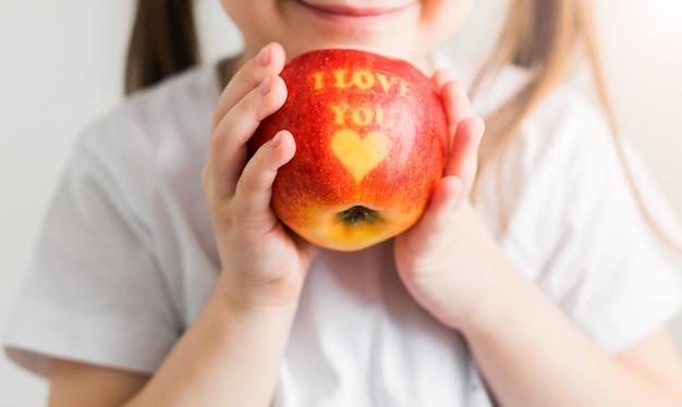 Маленькая девочка в белой футболке держит в руках яблоко с надписью i love you. вертикальное фото
