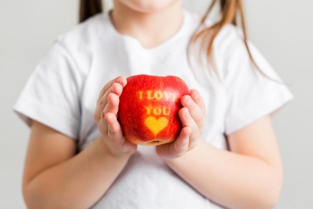 Маленькая девочка в белой футболке держит в руках яблоко с надписью i love you. ветеринарное фото