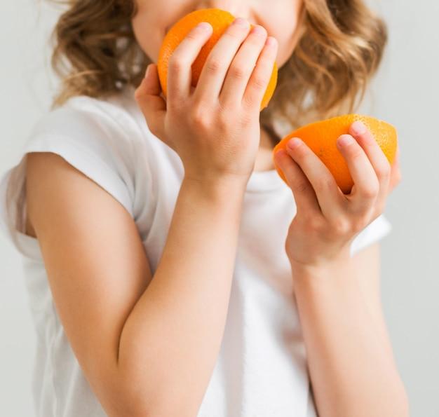 白いtシャツを着た小さな女の子が、オレンジ色のスライスを2つ手に持って、それらを嗅ぎます。縦の写真