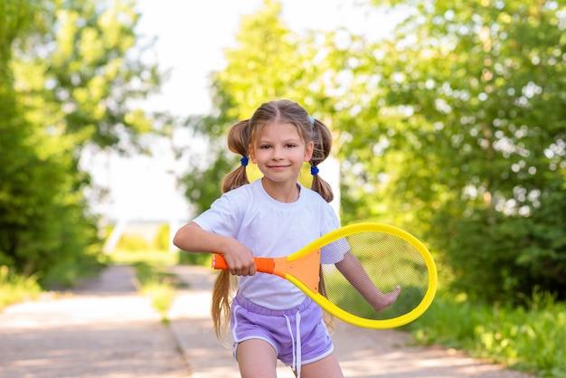Маленькая девочка в белой футболке играет в теннис летом.