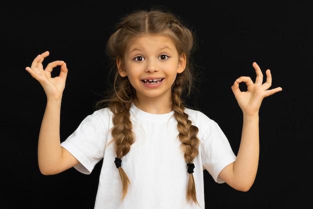 Маленькая девочка в белой футболке показывает знак ок.
