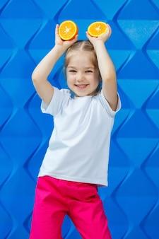 흰색 티셔츠를 입은 어린 소녀가 미소를 지으며 오렌지색 배경에 오렌지색 과일 두 개를 눈 앞에 들고 있습니다. 개념: 봄철 avitomnosis와의 싸움.