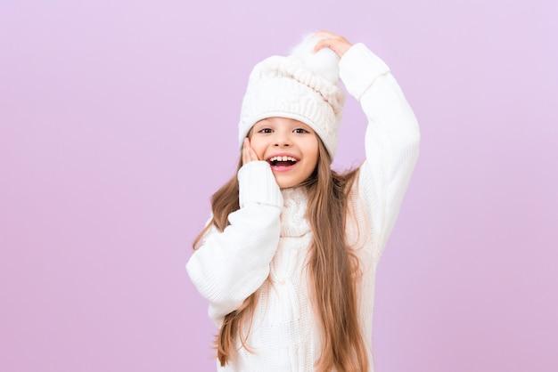 겨울 모자를 쓴 어린 소녀는 한 손은 뺨에, 다른 한 손은 모자에
