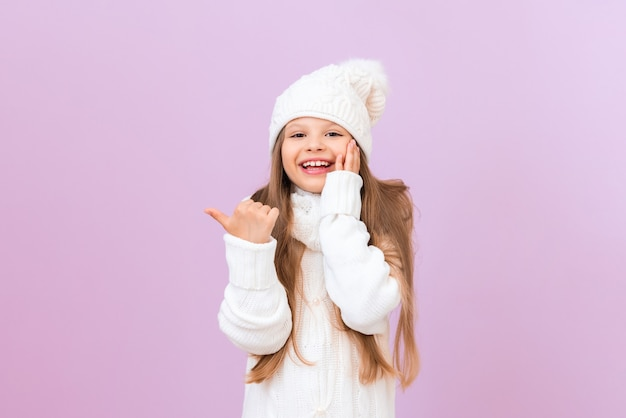 겨울 모자를 쓴 어린 소녀가 엄지손가락으로 옆을 가리킵니다.