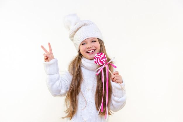 겨울 스웨터와 모자를 쓴 어린 소녀는 맛있는 롤리팝을 들고 흰색 외진 배경에 미소를 짓고 있습니다.