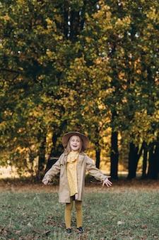 黄色いドレスとベージュのコートを着た少女が秋の公園を散歩