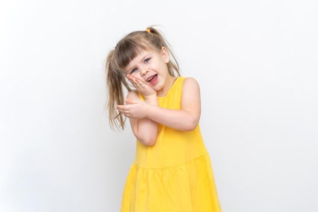 노란 드레스를 입은 어린 소녀가 치통을 앓고 있습니다.