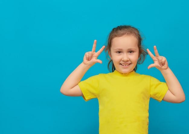 파란색 배경에 그녀의 손에 세 손가락을 보여주는 노란색 티셔츠에 어린 소녀