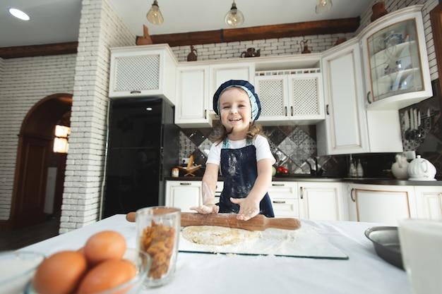 Маленькая девочка в фартуке и шляпе от шеф-повара раскатывает тесто для печенья, смеясь.