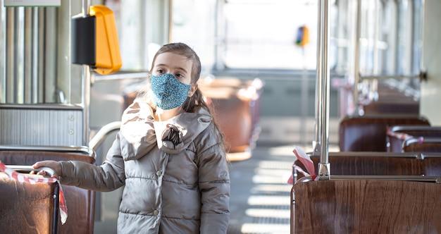 パンデミックコロナウイルスの最中、空の公共交通機関にいる少女。