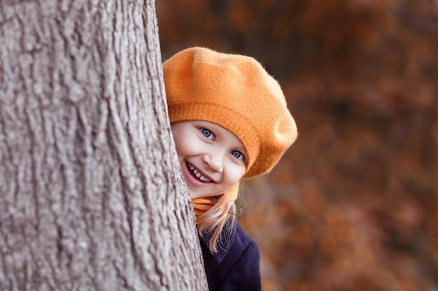 오렌지 베레모를 입은 어린 소녀가 나무 뒤에서 밖을 내다본다