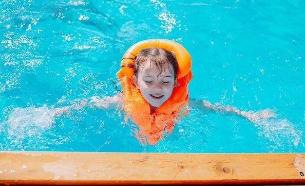 オレンジ色の救命胴衣を着た少女がプールで泳ぐ