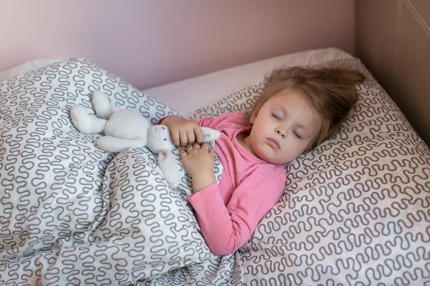 ベッドの中で小さな女の子がおもちゃで寝ています