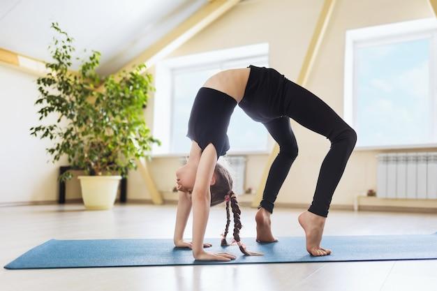 검은 운동복을 입은 어린 소녀가 요가를 연습하고 체조 매트, urdhva dhanurasana 포즈에서 다리 운동을 수행합니다.