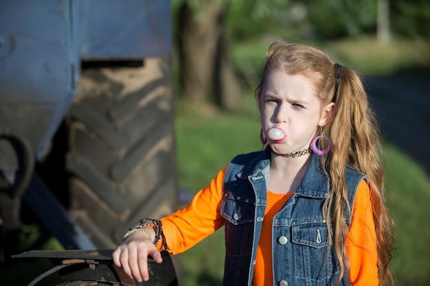 Маленькая девочка в яркой одежде надула жевательную резинку.