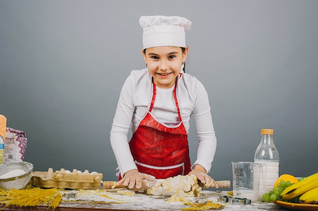 料理の帽子の少女が夕食を準備しています Premium写真