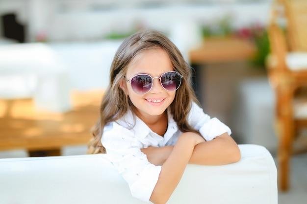 카메라 앞에서 긴 곱슬 머리 미소와 테라스 배경에 유행 안경에 어린 소녀. 여름, 재미, 가족 및 휴가 개념. 두 패션 포즈