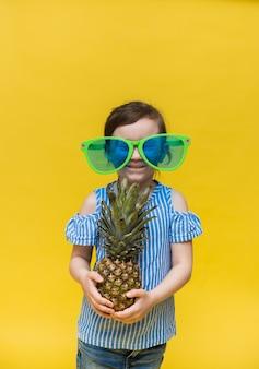 面白い大きなメガネの少女は、テキストの場所と黄色の壁にパイナップルの果実を保持します
