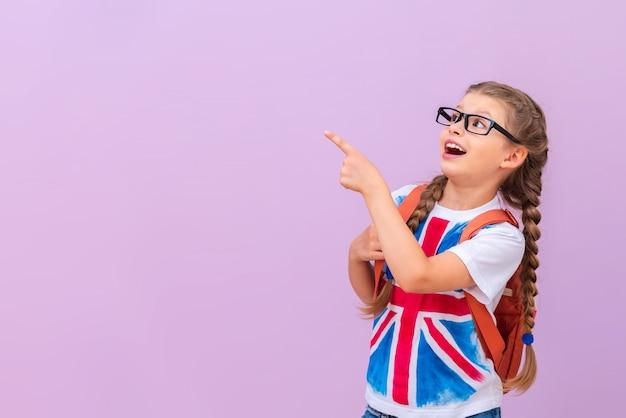 안경을 쓰고 배낭을 메고 영국 국기가 달린 셔츠를 입은 어린 소녀가 귀하의 광고를 가리킵니다.