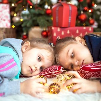 집에서 옷을 입은 어린 소녀가 선물 상자 근처의 크리스마스 트리 아래에 누워 있습니다.