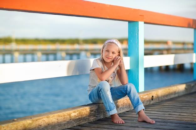 청바지와 티셔츠를 입은 어린 소녀가 발트해 근처 부두에 앉아 있습니다. 리투아니아 팔랑가