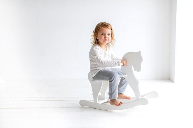 明るい服を着た少女が白いインテリアの馬の担架に座っています