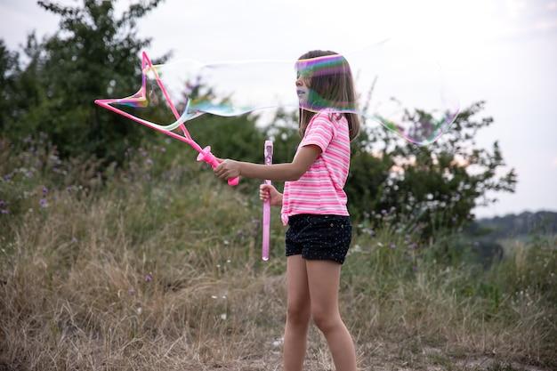 自然界の小さな女の子が大きなシャボン玉で遊んでいます。
