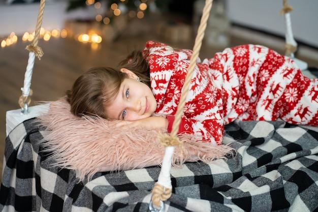 잠옷을 입은 어린 소녀는 축제의 밤에 잠을 잘 수 없습니다. 크리스마스 마술 동화. 행복한 어린 시절