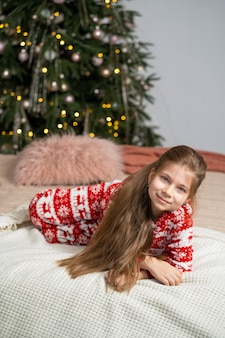 Маленькая девочка в пижаме рано утром нашла под елкой подарок от санты. рождественская волшебная сказка. счастливое детство.