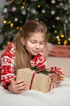 Маленькая девочка в пижаме рано утром нашла под елкой подарок от санты