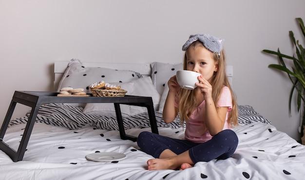 パジャマ姿の少女がパンのトレイとお茶のマグカップを持ってベッドに座っています