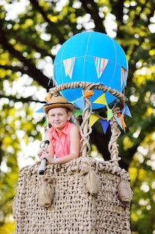 Маленькая девочка в розовой одежде с подзорной трубой в руках в корзине синего воздушного шара смотрит вдаль и улыбается.