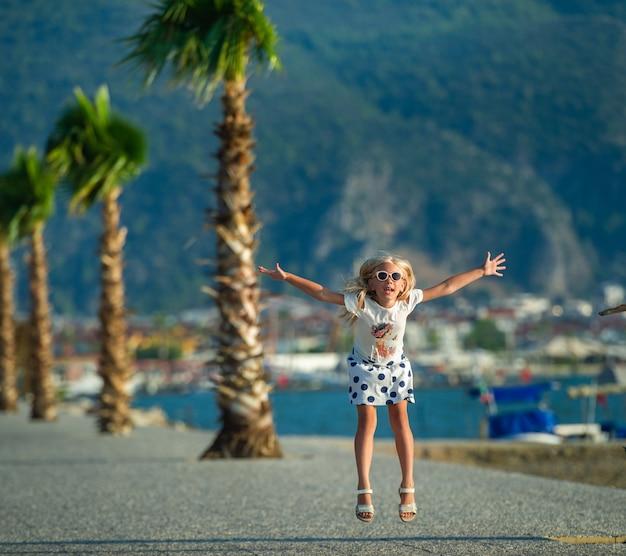 Fethiye.turkeyのヤシの木の近くの桟橋でショートパンツとタンクトップの小さな女の子が跳ねます。