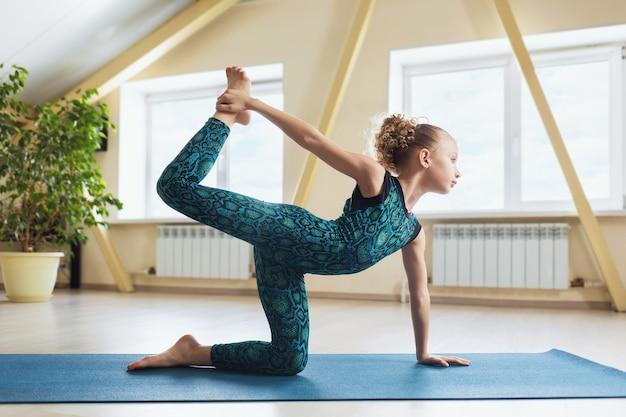 Маленькая девочка в спортивной одежде, практикующая йогу, выполняет упражнение ардха дханурасана в позе полукруга.