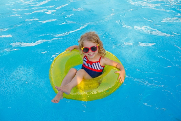 선글라스와 수영복을 입은 어린 소녀가 여름에 풍선 원에 수영장에서 수영합니다.