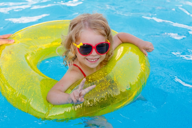 Маленькая девочка в солнцезащитных очках и купальнике плавает в бассейне на надувном круге летом