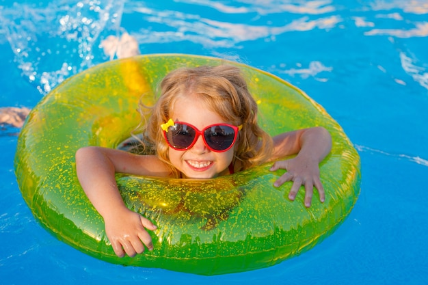 サングラスと水着を着た少女が夏に膨らませて円を描くようにプールで泳ぐ