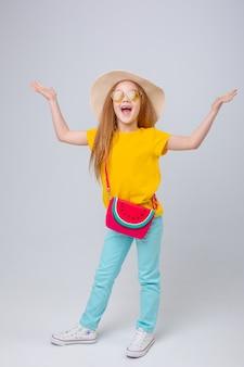 흰색 배경에 선글라스와 여행자 모자를 쓴 어린 소녀