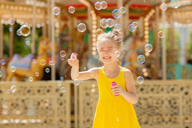 Маленькая девочка в солнечных очках дует мыльные пузыри в парке летом