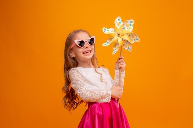 Маленькая девочка в солнечных очках держит игрушку-вертушку на желтом фоне