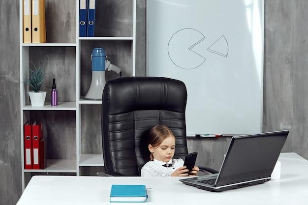 회사원 이미지의 어린 소녀가 책상에 앉아 전화 통화를 하고 있다