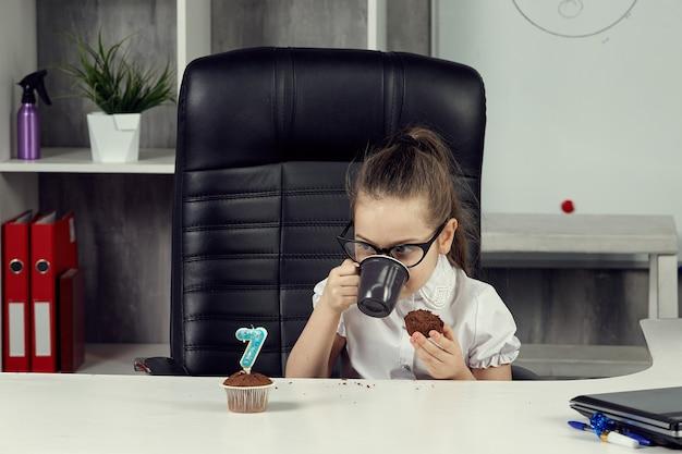 회사원 이미지의 어린 소녀는 테이블에 앉아 점심을 먹는다