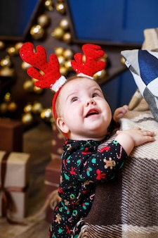 Маленькая девочка в теплом свитере сидит под елкой с игрушками и подарками с рогами на голове. счастливое детство. атмосфера новогоднего праздника