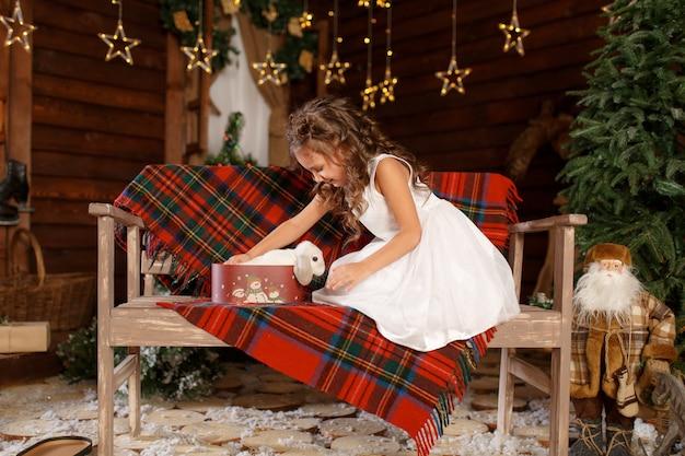 白いウサギのベンチとオープンボックスに座っている白いドレスの少女。夜のクリスマスツリーのインテリアの魔法の光