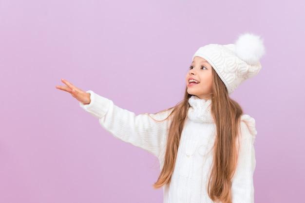 겨울 옷을 입은 어린 소녀가 광고를 보고 미소를 짓고 있습니다.