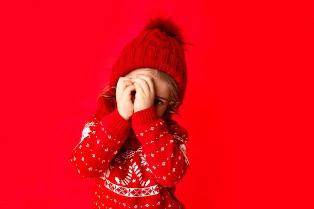 Маленькая девочка в зимней одежде шпионит на красном фоне. новогодняя концепция, место для текста