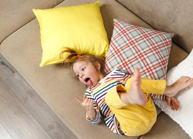 노란색 바지와 화려한 티셔츠를 입은 어린 소녀가 소파에 등을 대고 혀를 보여 주면서 놀린다. 어린 이용 홈 게임. 노란색 베개.