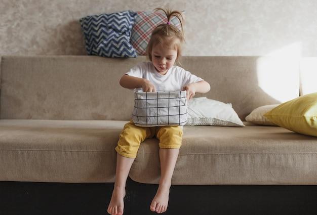 노란색 바지와 흰색 티셔츠를 입은 어린 소녀가 소파에 앉아 옷을 깔끔하게 접어 보관 상자에 넣습니다. 엄마의 비서.