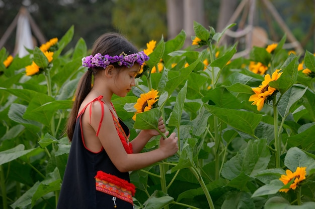 어린 소녀가 꽃밭에서 감탄하고 즐기고 있습니다.