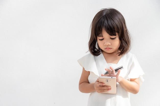 Маленькая девочка сосредоточена на телефоне, посмотрите на смартфон, концепция технологии для детей, вид профиля, изолированные на белом фоне, скопируйте пространство